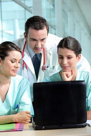 Un team di medici professionisti di consulenza cartelle cliniche dei pazienti Archivio Fotografico