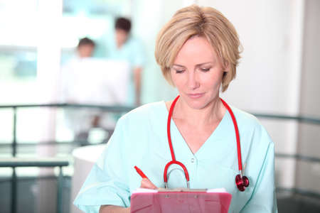 A female doctor taking notes on a clipboard in the middle of a big room. photo