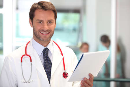 male facial: Hospital doctor checking patient notes Stock Photo