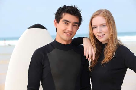 Young surfing couple in wetsuits photo