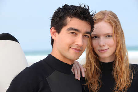 Young couple in wetsuits at the beach photo