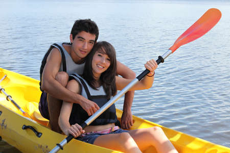 young man and woman doing canoe on a lake photo