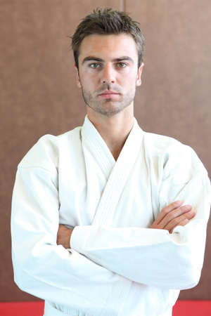 Judo practitioner standing on a mat with his arms folded photo