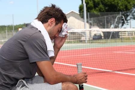sudando: El tenista con una toalla Foto de archivo