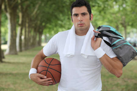 wet t shirt: 30 years old sportyman holding a basket ball and a sports bag