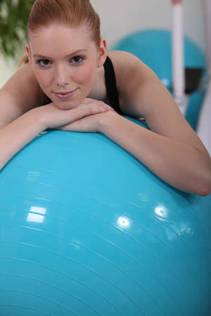 Young woman leaning on fitness ball photo