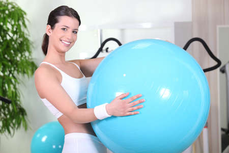 Smiling woman with an exercise ball in a gym photo