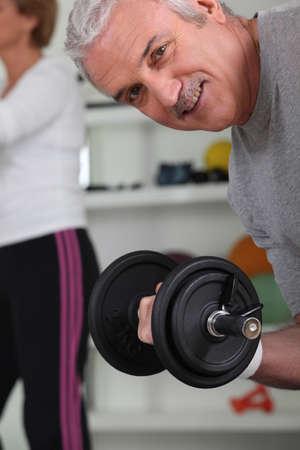 circular muscle: Smiling mature man lifting barbell