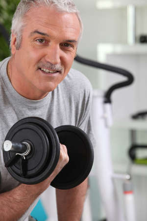 Mature man working out with a dumbbell photo