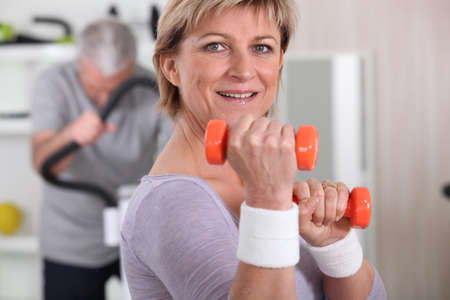 50 to 60: senior woman doing exercises with a dumbbell Stock Photo