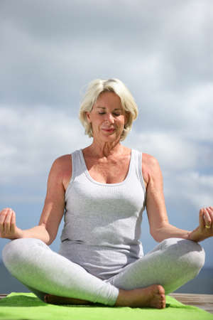 Middle-aged woman sat in yoga position photo