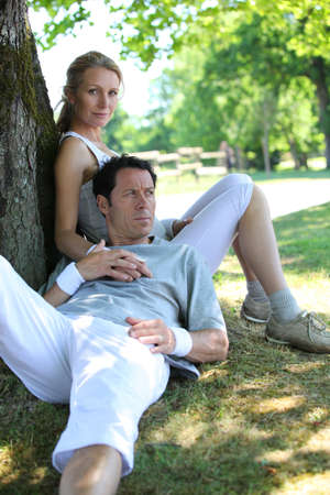 45 49 years: Portrait of sporty couple relaxing by tree