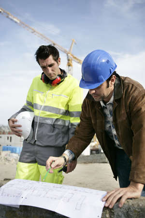 construction site helmet: Foreman and colleague examining plans