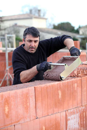 Man pouring wet cement on to wall Stock Photo - 11612500