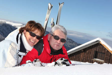Mature couple lying in the snow outside their ski cabin