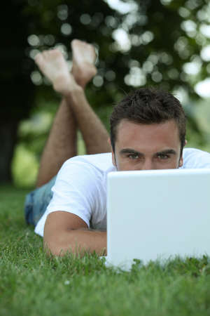 Man lying on grass in front of laptop computer photo