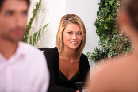 Woman in a black dress sitting in a restaurant photo
