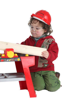 protective wear: Child playing with a toy workbench Stock Photo