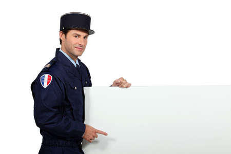Man in a French gendarme uniform pointing at a blank board ready for text or image Stock Photo - 11674345