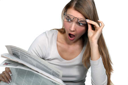 Woman shocked reading newspaper photo