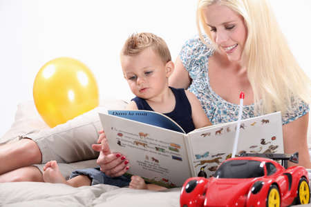 babysitter: Woman reading a book to her son Stock Photo