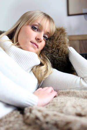 Woman snuggling up on her sofa photo