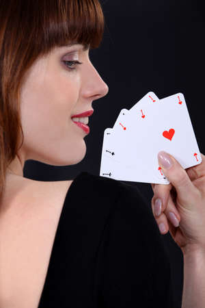 Woman poker player with four aces in hand photo