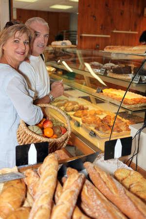 french pastry: pareja madura en una panader�a Foto de archivo