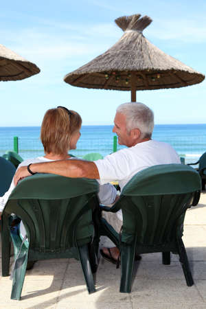 Middle-aged couple sat by the seafront photo