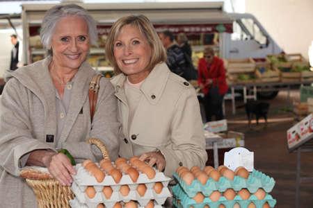 granja avicola: Madre e hija comprando huevos en un mercado