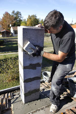 Bricklayer building a post Stock Photo - 11674631