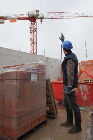non verbal communication: Worker making a sign to another worker Stock Photo
