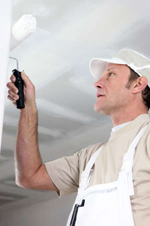 man painting: Man painting a room white