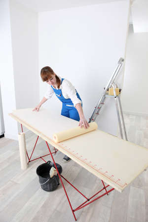 house under construction: Decorator measuring wall paper Stock Photo