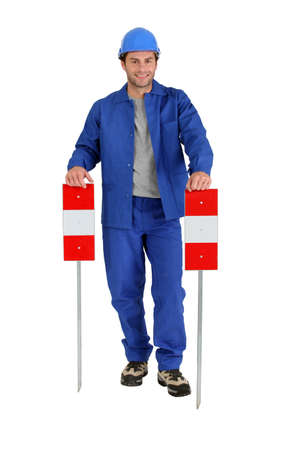Builder holding road signs. Stock Photo - 11754529