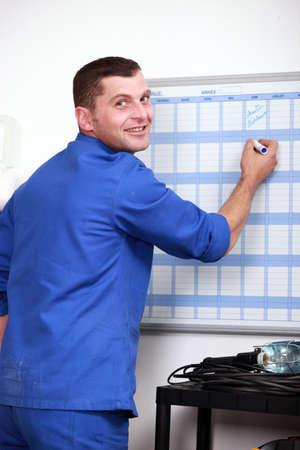 filling in: Man filling in wall schedule