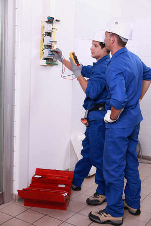 Two electricians inspecting electrical, power supply photo