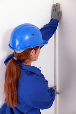 jumpsuite: female worker wearing a blue jumpsuite is checking the wall