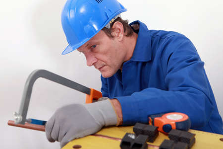 sawing: Industrial worker sawing copper pipe Stock Photo