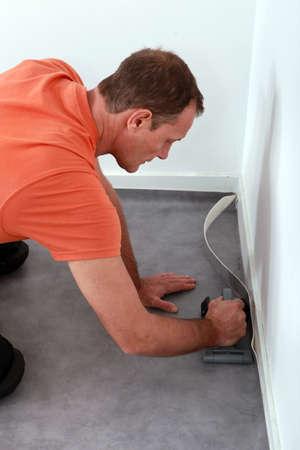 smoothen: Workman putting down linoleum flooring