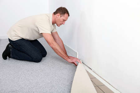qualified worker: craftsman fitting a carpet Stock Photo