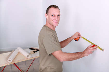 Man measuring wall photo