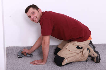 man on all fours stapling carpet Stock Photo