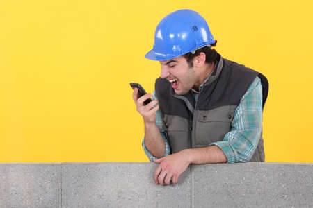 delirious: Builder shouting down his cellphone Stock Photo