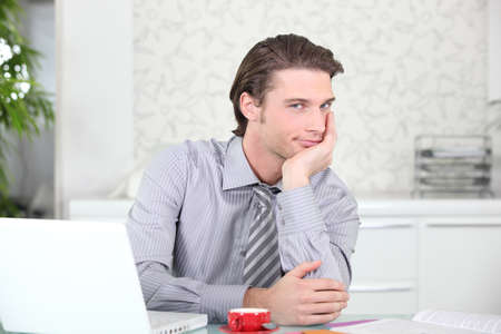 grin: Handsome young man with an expresso next to his laptop