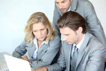Three executives examining laptop computer photo