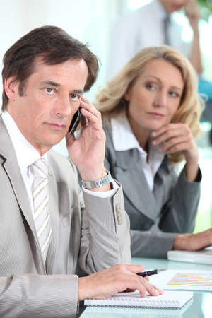 perturbed: A businessman using a mobile phone and being observed by a businesswoman during a meeting. Stock Photo