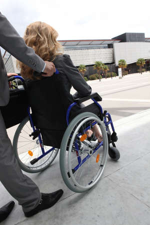 Female executive being pushed in wheelchair photo