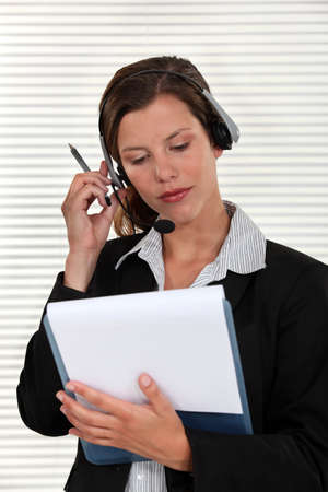 Woman adjusting her headset and holding a clipboard photo