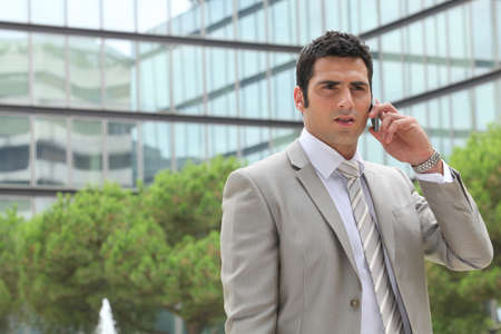 Businessman outdoors talking on phone photo